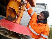 Dílenský mechanik Milan Bažant seřizuje rozmetadlo posypového vozidla.