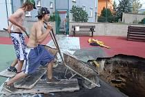 Kráter, který na dětském hřišti ve Lhotce nad Labem tento týden vznikl, kamennou moučkou zasypávali chlapci Filip, Roman (na snímku) a Tomáš z Vrbičan. Podle pracovníků firmy, která byla pracemi pověřena, padne do díry odhadem 10 fůr auta Avia.