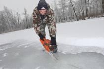OSM CENTIMETRŮ byl v sobotu ráno silný led na Doksanském rybníku u Ohře. Rybáři proto vyrazili na zamrzlou hladinu se sekerami a pilami, aby do ledu udělali otvory.