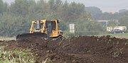 Průmyslová zóna u Lovosic se začíná stavět. Buldozér odstraňuje vrstvu úrodné zeminy.