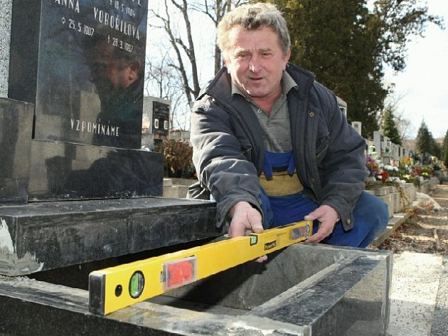 Na městském hřbitově v Litoměřicích dělníci v těchto dnech zpevňují podloží hrobů.  Po rozebrání pomníků pokládají  do země betonové nosníky a na ně urnové hroby znovu skládají. Ladislav Bartoš srovnává základ jednoho z pomníků.