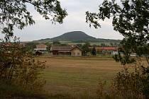 Obec Vražkov a za ní je hora Říp.
