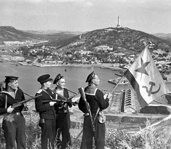 Rusové vztyčují vlajku nad dobytým přístavem Port Arthur vroce 1945.