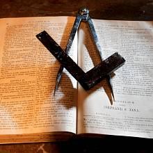 Atributy svobodných zednářů - úhelník, kniha a kružidlo.