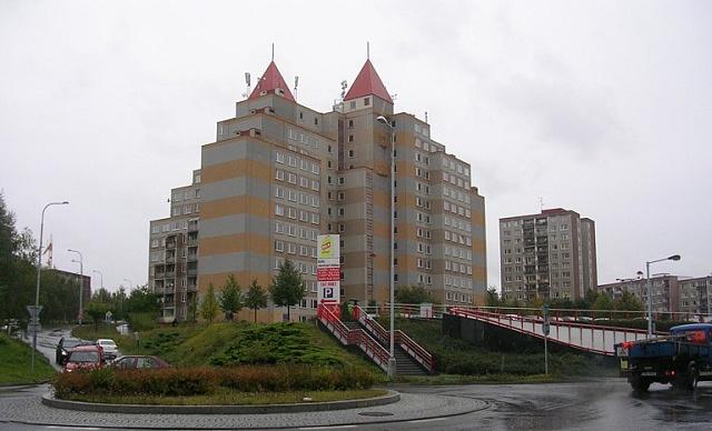 Snaha ozvláštnit fádní sídliště vedla koncem 80.let kbizarnostem. Centrální panelák na pražském sídlišti Barrandov měl samoúčelnými jehlany na střeše připomínat kostel.