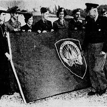 První vrchní velitel ozbrojených sil NATO v Evropě generál Dwight D. Eisenhower pózuje u původní vlajky aliance