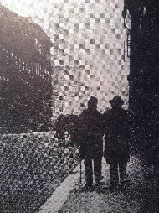 Jan Neruda, podporovaný při chůzi veřejným posluhou, na jedné z posledních procházek Prahou