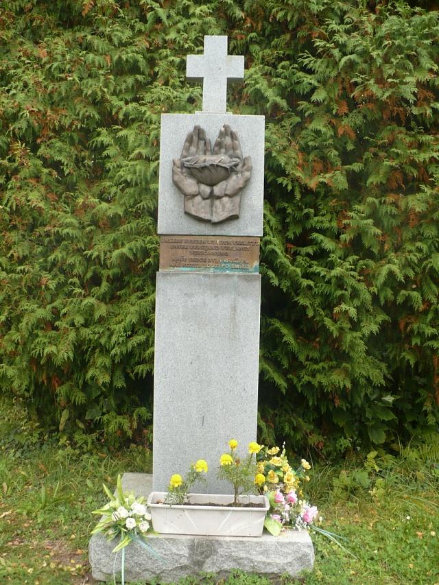 Pomník obětem odsunu na lanškrounském hřbitově snápisem vobou jazycích: 'Naše srdce byla raněna, náš rozum touží po smíru'.