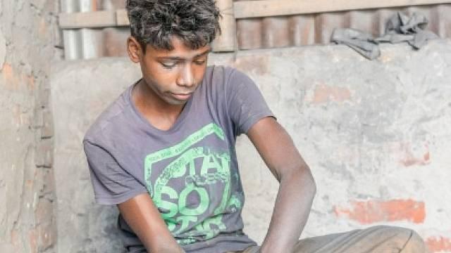 Chlapec v dílně. Dháka, Bangladéš.