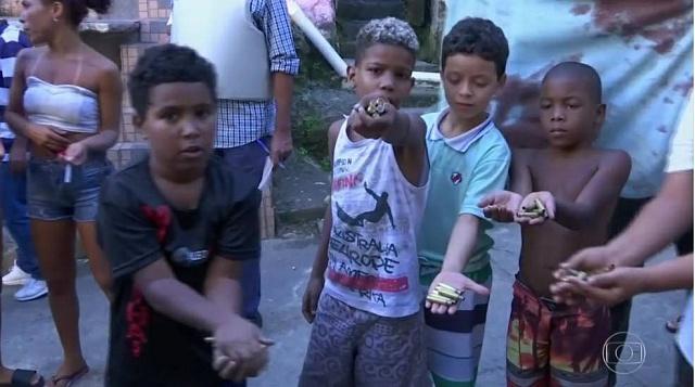 Děti z Ria de Janeira ukazují nalezené nábojnice pocházející z pouličních přestřelek