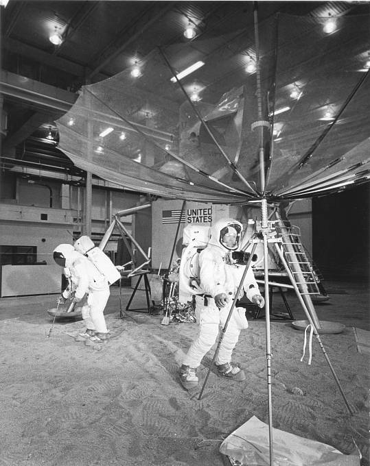 Snímek z tréninkové haly NASA, duben 1969. Buzz Aldrin (vlevo) sbírá vzorek horniny, Neil Armstrong s kamerou na hrudi kontroluje jednu z antén.