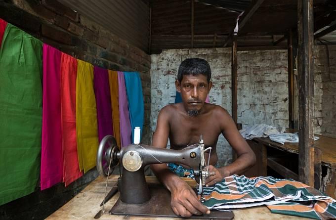 Muž v Dháce u šicího stroje