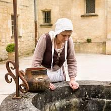 Žena v historickém oblečení pracující na staré vodní studně francouzského středověkého hradu