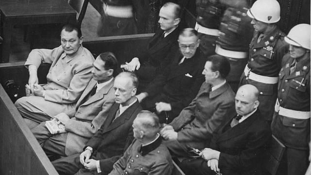 Nacističtí prominenti před soudem v Norimberku: přední řada zleva Göring, Hess, Ribbentrop a Keitel, zadní řada zleva Dönitz, Raeder, Schirach a Sauckel