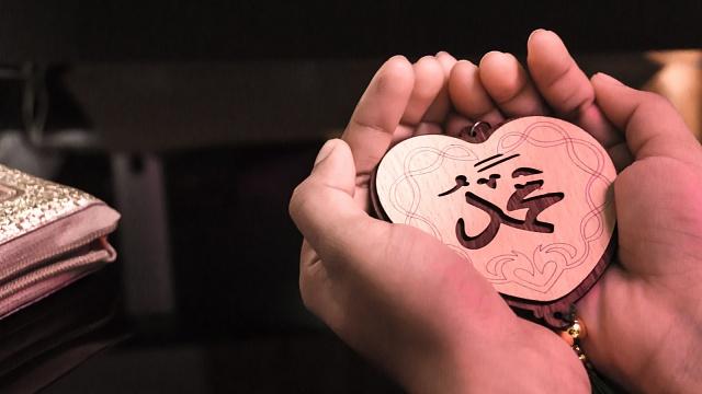 """Muslimská žena drží značku ve tvaru srdce, 'lásku', varabštině """"Muhammad"""" - anglický význam proroka Mohameda."""