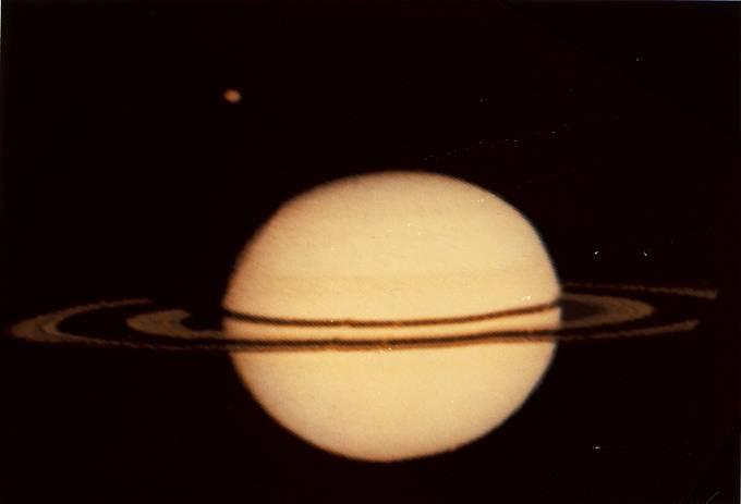 Pioneer 11, první sonda ze Země, která dosáhla oblast Saturnu. Na snímku planeta spolu s měsícem Titanem (v levé horní části). Foto z roku 1979.