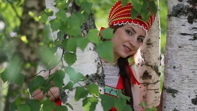 Slovanská dívka se ukrývá za březovým kmenem