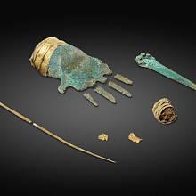 bronzová ruka a další artefakty nalezené v hrobě.