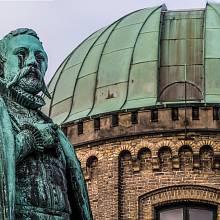 Socha Tychona Brahe před zastřešenou observatoří vedle zámku Rosenborg v dánské Kodani
