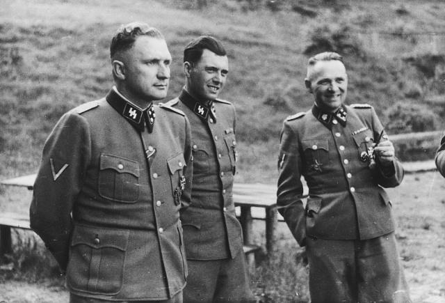 """Tři vysocí důstojníci SS při hovoru mimo Osvětim, v """"Solahütte"""". Osvětim, Polsko, 1944.Zleva doprava: Richard Baer (velitel Osvětimi), Dr. Josef Mengele a Rudolf Hoess ( bývalý velitel Osvětimi)."""