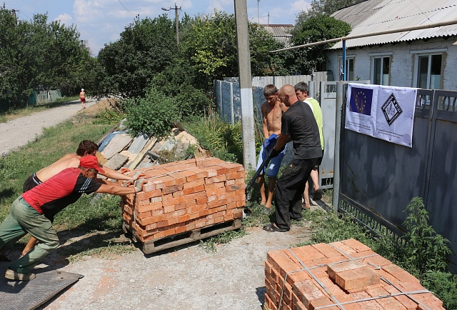 Pracovníci Člověka vtísni pomáhají lidem vblízkosti frontové linie sopravou domů.