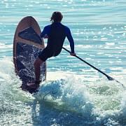 Zkušenější surfaři dokážou na paddleboardu sjíždět i vlny.