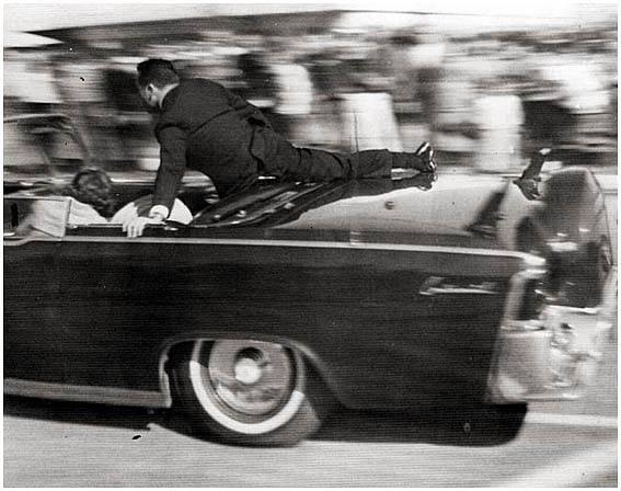Agent Clint Hill bezprostředně po výstřelech naskočil na stupátko a zatlačil zpět do vozu Jacqueline Kennedyovou