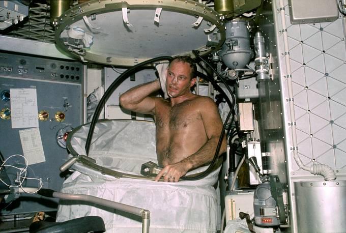 Astronaut Jack R. Lousma z druhé posádky si dává na Skylabu sprchu ve sprchové kabince