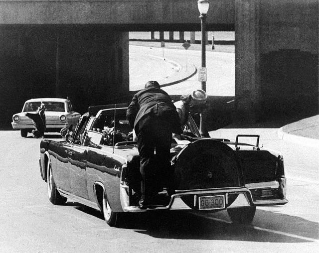 Agent Clint Hill na stupátku Kennedyova vozu