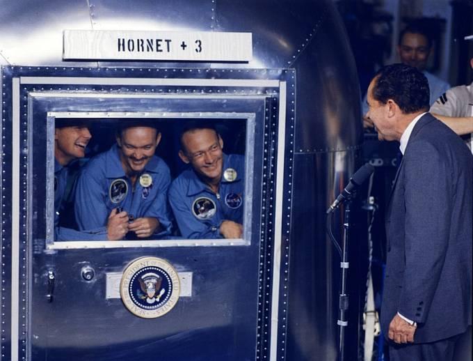 Armstrong, Collins a Aldrin se z izolačního kontejneru zdraví s prezidentem USA Richardem Nixonem. Propuštěni byli 17 dní po přistání.