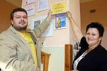 Erika Pospíšilová z občanského sdružení Kostičky a Pavel Brož z o.s. Dobroděj umisťují symbolický šek v budově lounské speciální základní školy.