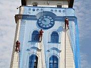 Radnici v Žatci stále halí modré sítě. Snímek z července 2015, kdy je odborná firma instalovala