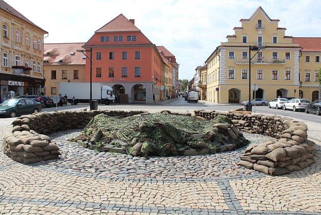 Natáčení filmu Jojo Rabit vcentru Žatce. Kašna na náměstí je obklopena pytli spískem.