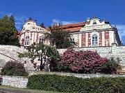 Zámek ve Stekníku s italskými terasovitými zahradami akvetoucími popínavými růžemi.