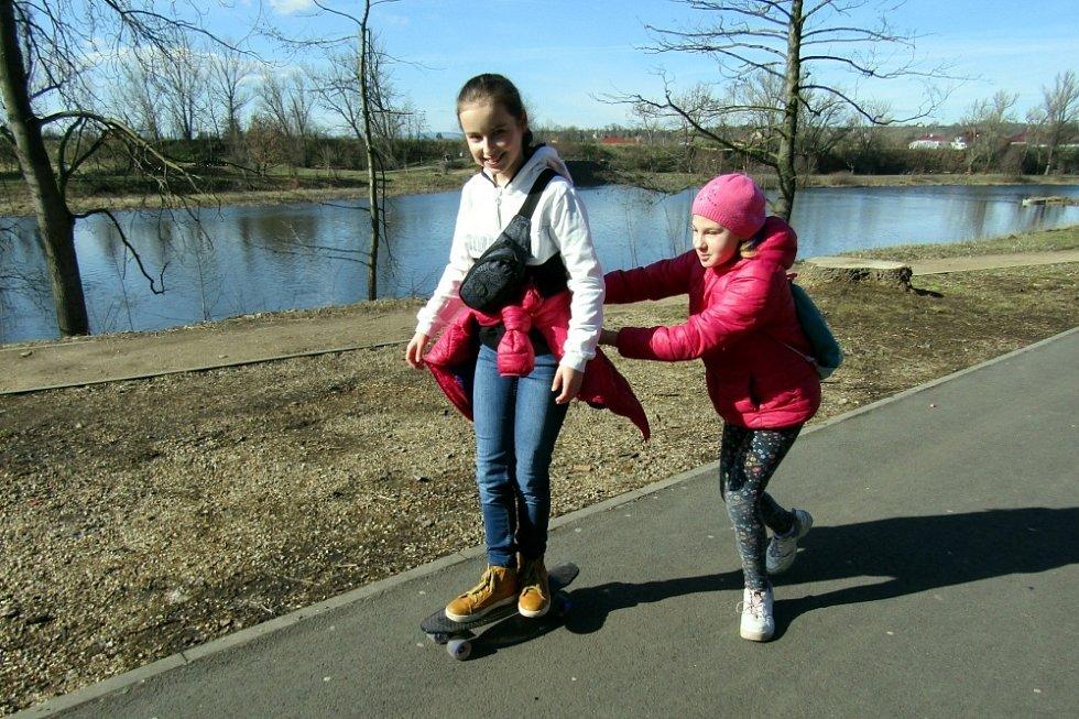 Jarní počasí vytáhlo lidi k řece. V akci byly brusle, kola i hole.