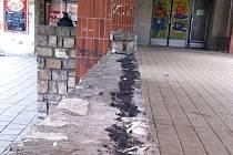 Zídka na sídlišti potřísněná černou kolomazí