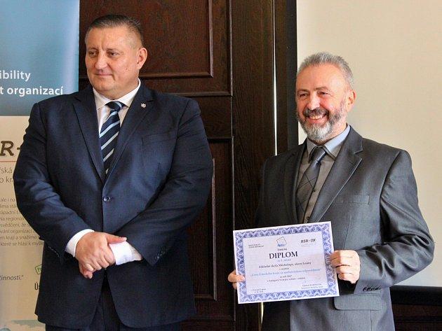Cenu z rukou náměstka hejtmana Ústeckého kraje Martina Kliky (vlevo) převzal ředitel ZŠ Měcholupy Zdeněk Dosedla.