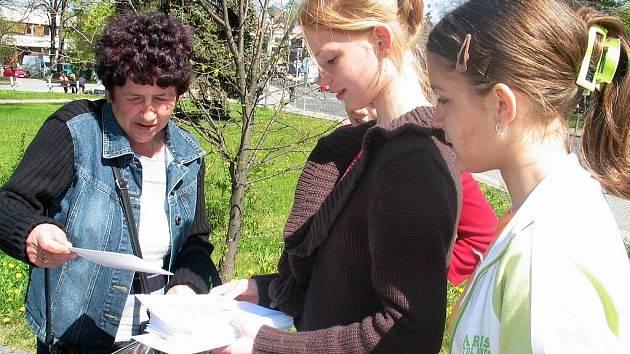 Studenti gymnázia nabízejí pohlednice.
