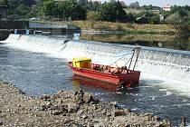 Práce u jezu nyní probíhají pomocí potápěčů, jako zázemí jim slouží loďka uvázaná na lanech.