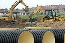 Stavební stroje pracují na výkopu pro kanalizaci poblíž stadionu Flóra v Žatci, kde se v současné době připravují sítě pro dalších 18 stavebních parcel.