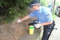 Strážník sbírá injekční stříkačku.