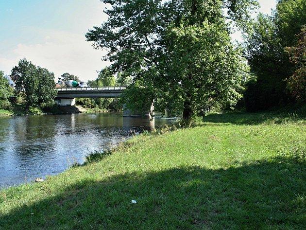 Pěšina na pravém břehu řeky Ohře pod jatkami poblíž mostu silnice Plzeň Most. Na podzim tam vyroste tři metry široká asfaltová cyklostezka.