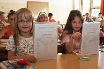 Veronika Bartošová a Lucie Rokosová (zleva) ukazují vysvědčení, které v pátek s dalšími dětmi převzaly na ZŠ ve Školní ulici v Lounech.