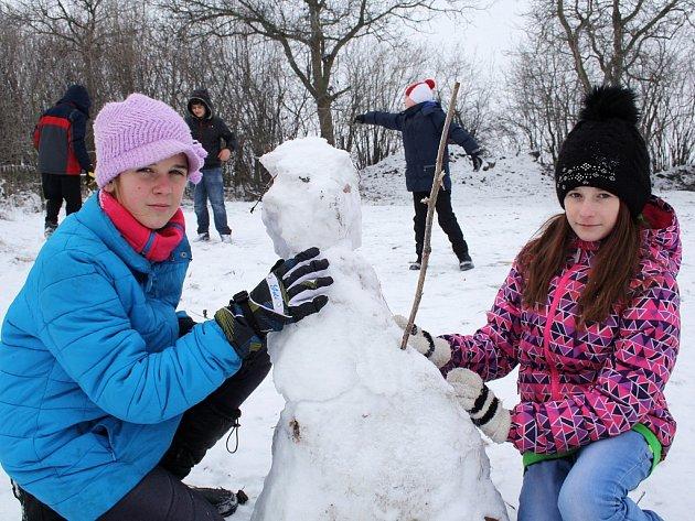 Karolína Failová (vlevo) a Natálie Müllerová staví a upravují sněhuláka.