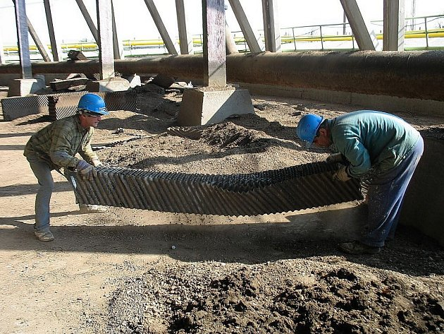 Dělníci přenášejí část chladícího systému k věži v Počeradech.