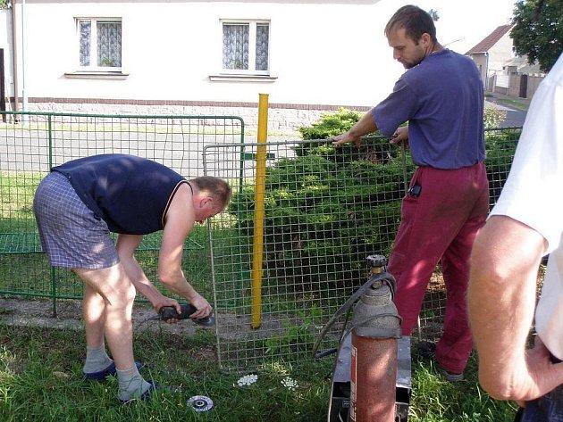 Tatínkové v Jimlíně pracují při brigádě na dětském hřišti.