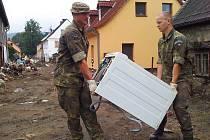 Vojáci ze žatecké brigády odklízejí pračku, kterou zničila povodeň v jednom z domů na severu Čech.