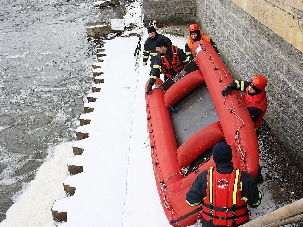 Hasiči snášejí člun k hladině Ohře přímo pod jezem