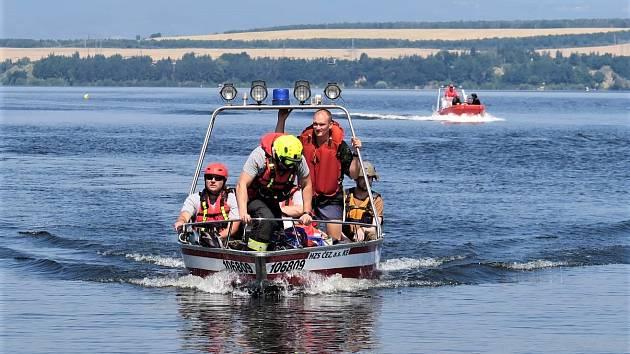"""Mezi """"zachránce tonoucích"""" patřila i profesionální jednotka hasičů ze Skupiny ČEZ, jejichž pobočná stanice požární ochrany se nachází v nedaleké Elektrárně Tušimice. V pozadí člun Vodní záchranné služby ČČK."""