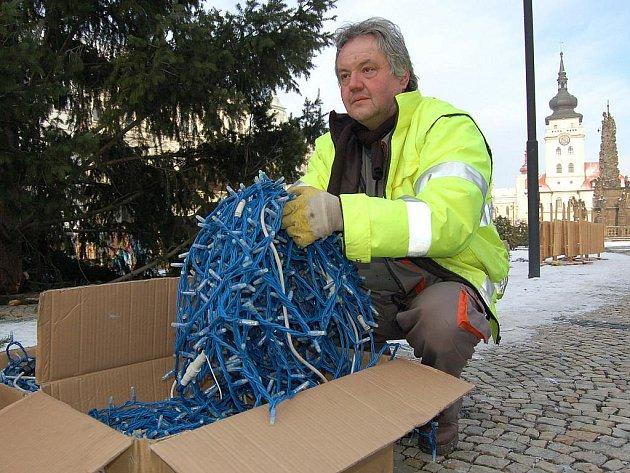 Drahoslav Mašek skládá světelné ozdoby do bedny u vánočního stromu na náměstí Svobody v Žatci.